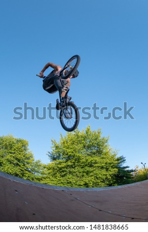 Biker jump high from jump box ramp performing big air trick.