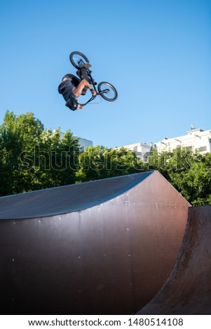 Biker jump high from jump box ramp performing dangerous backflip trick.