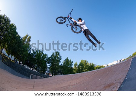 Biker jump high from jump box ramp performing dangerous superman trick.