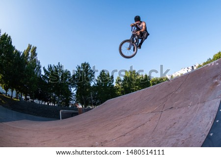 Biker jump high from jump box ramp performing dangerous tail grab trick.