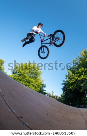 Biker jump high from jump box ramp performing dangerous tail whip trick.