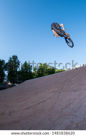 Biker jump high from jump box ramp performing dangerous 360 trick.