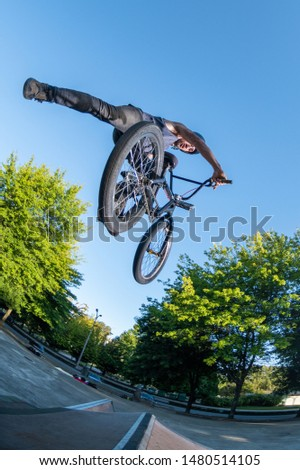 Biker jump high from jump box ramp performing foot off trick.