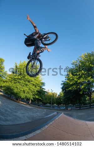 Biker jump high from jump box ramp performing hands off the handlebars trick.