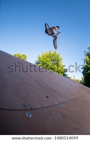 Biker jump high from jump box ramp performing look back trick.