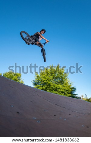 Biker jump high from jump box ramp performing 360 trick.