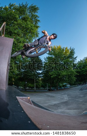 Biker jump high from jump box ramp performing wall ride trick.