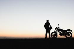 Biker man and motorcycle,Young man rider trendy motorbik had stopped to rest during the trip to see the light of nature,light of the sky between change day to night. silhouette wallpaper concept