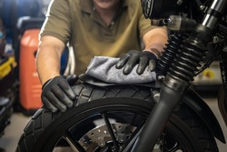 Biker man cleaning motorcycle , Polished and coating Wax Spray on front fender. repair and maintenance motorcycle concept.