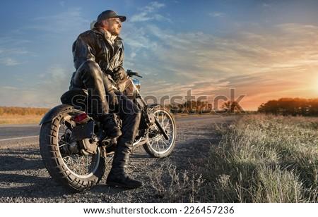 Biker man looking on sunrise
