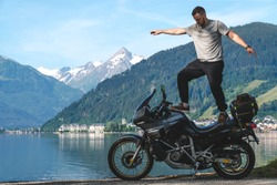 Biker man stand on top of a motorcycle keeps balance, extreme. hobby concept, adventure on two wheels. Sunny summer day in the Alpine mountains. Zell am see lake on background Austria. Copy space