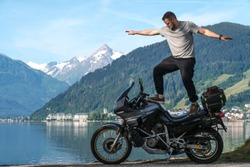 Biker man stand on top of a motorcycle keeps balance, extreme. hobby concept, adventure on two wheels. Sunny summer day in the Alpine mountains. Zell am see lake on background Austria.