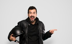 Biker man surprised and pointing finger to the side over isolated grey background