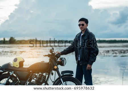 Biker man with his motorbike beside the natural lake and beautiful, enjoying freedom and active lifestyle, having fun on a bikers tour.sunset background and sky. #695978632