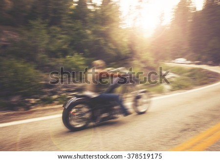 biker on mountain highway, riding around a curve with a motion blur toned with a retro vintage instagram filter app or action