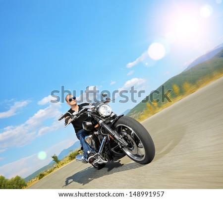 Biker riding a customized motorcycle on an open road, shot with a tilt and shift lens