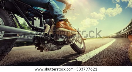 Biker riding on a motorcycle. Bottom view of the legs in leather boots.