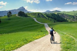 Biker riding scenic path in beautiful summer mountain scenery , Dolomites Italy, European Alps.