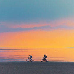 Biker silhouette riding along dune beach at calm cloud sunset view on mtb bike Sporty company group of friends on bicycle outdoors, cyclist mountain biking city park path concept. dad son fit exercise