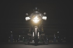 Biker sitting on his motorcycle on a night parking area.