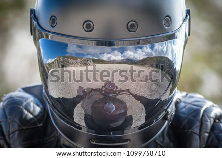 Biker stay on his motorcycle with a desolated mountain landscape reflected on his helmet visor