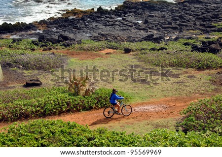 Biker takes the rugged trail along lava lined beach on Kauai, Hawaii.  Biker has on blue shirt and shorts. - stock photo