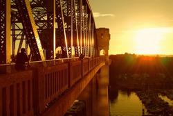 Bikers crossing Burrard bridge in sunset, Vancouver, Canada