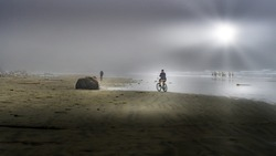 Bikers in Dense Fog biking on the Beach in Cox Bay at the Pacific Rim National Park on Vancouver Island, British Columbia, Canada