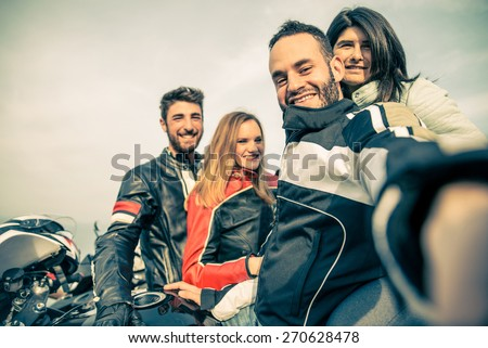 Bikers taking selfie with camera - Four smiling friends driving racing motorcycles with their girlfriends  - Two happy couples stop in a panoramic view point and photographing themselves