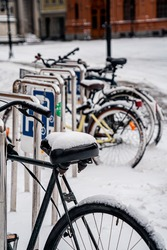 bikes in the snow is parked in the city bike parking