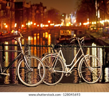 Bikes parked on bridge in Amsterdam at night