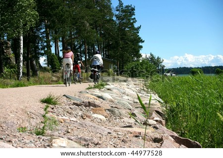 Biking family a sunny day, next to the sea, sea-grass on the side with blue sky
