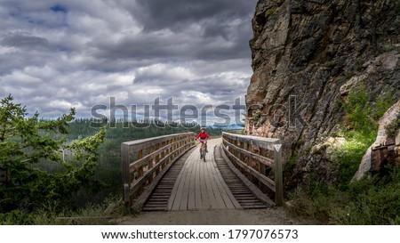 Biking over the Wooden Trestle Bridges of the abandoned Kettle Valley Railway in Myra Canyon near Kelowna, British Columbia, Canada Stockfoto ©