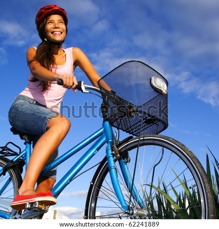 Biking under deep blue sky in the countryside of Jutland, Denmark during summer. Beautiful happy woman.