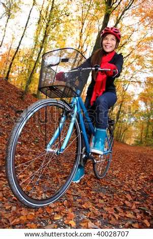Biking, Woman on bike in autumn forest. Beautiful mixed asian / caucasian model.