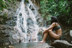 Bikini girl sitting next to idyllic tropical waterfall in Thailand