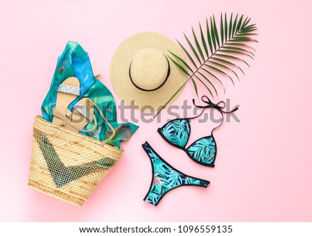 Bikini swimsuit with tropical print, silver glitter flat sandans, straw hat, wicker beach bag, sarong, tropical palm leaves on pink background. Overhead view of woman's swimwear and beach accessories. #1096559135