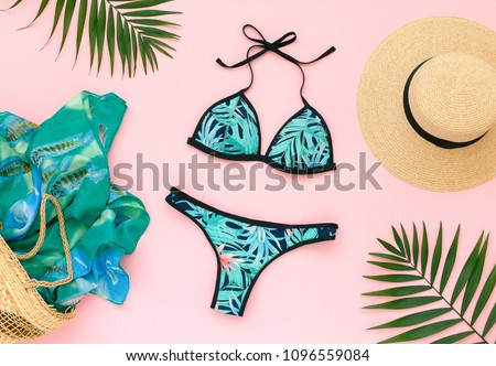 Bikini swimsuit with tropical print, straw hat, wicker beach bag, sarong and tropical date palm leaves on pink background. Overhead view of woman's swimwear and beach accessories. Flat lay, top view. Foto stock ©