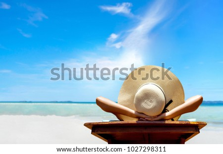 Bikini woman sexy in relax beach and resting resort in vacation on summer season with sunhat sitting chair sunbath with swimsuit alone at island lifestyle on weekend holidays