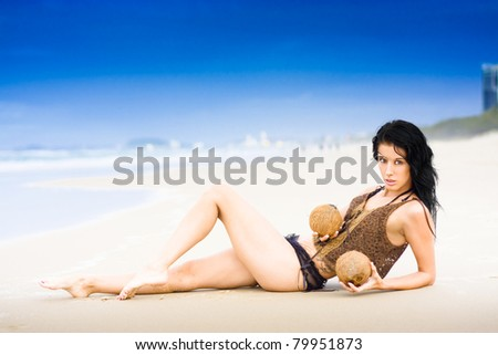 Bikini Woman Striking Sexy Pose And Holding Coconuts On A Beautiful White Sand Beach With Vivid Blue Sky Background