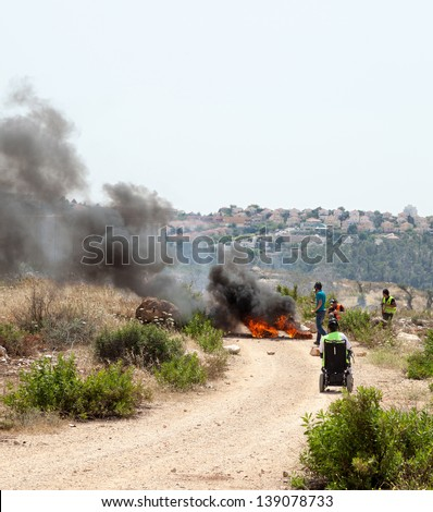 BIL'IN, PALESTINE - MAY 17: People walking by tires burning on the road leading to the wall of separation, on a protest against the Israeli occupation of Palestine on May 17, 2013 in Bil'in, Palestine