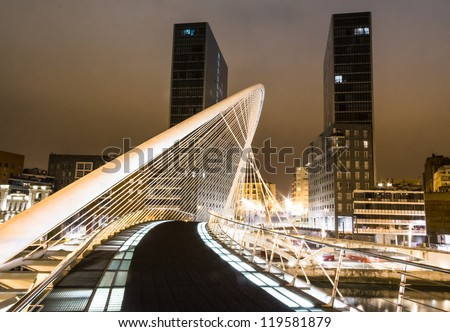 BILBAO, SPAIN - APRIL 02: Night view of Zubizuri bridge and Isozaki towers in the background, in Bilbao, Spain, on April 02, 2012. The bridge was designed by Spanish architect Santiago Calatrava