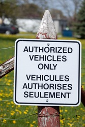Bilingual sign on a post stating authorized vehicles only.