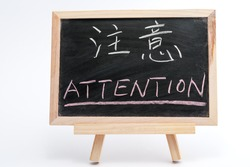 Bilingual word of Attention in both Chinese and English written on blackboard over white background