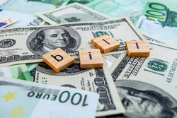 bill inscription on wooden cubes on the texture of us dollars and euro banknotes