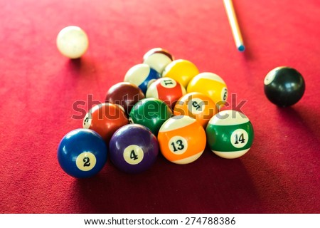 Billards pool game. Color balls in triangle, aiming at cue ball. Red cloth table , Pool balls on a red background