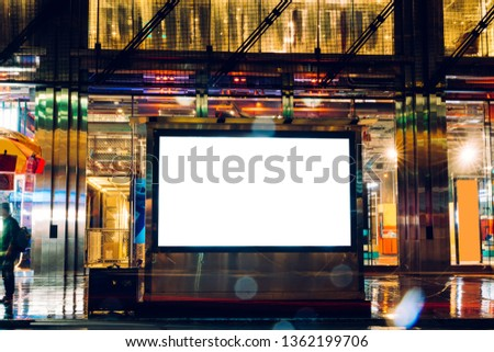 Billboard in rainy night with blank copy space screen for advertising or promotional publicity content, empty mock up Lightbox for information, blank display in urban street with city lights