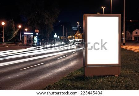 Billboard in the city street by night, blank screen