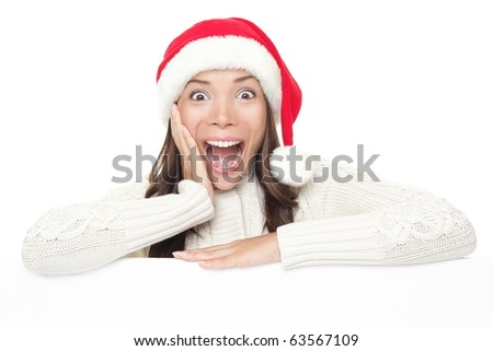 Billboard woman in santa hat leaning on banner for Christmas. Surprised asian beautiful happy model showing blank sign isolated on white background.