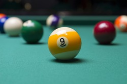 Billiard balls in a pool table. focus on the yellow ball